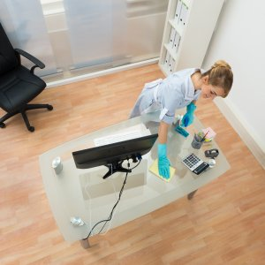High Angle View Of Young Maid Cleaning Desk In Office